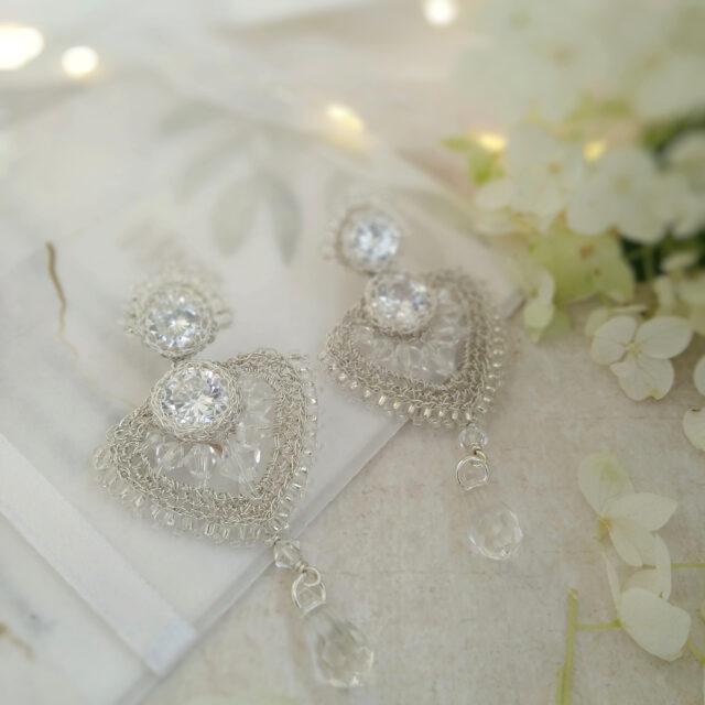 Biżuteria ślubna nazaproszeniu, obok delikatne kwiaty hortensji awtle bokeh