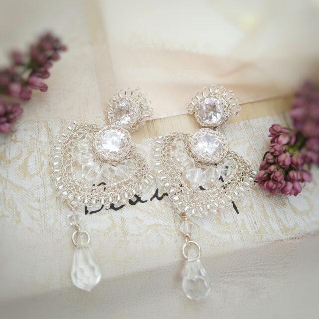 Bogate kolczyki ślubne leżą na ramce do zdjęć. Obok widać kwiat lilaka.