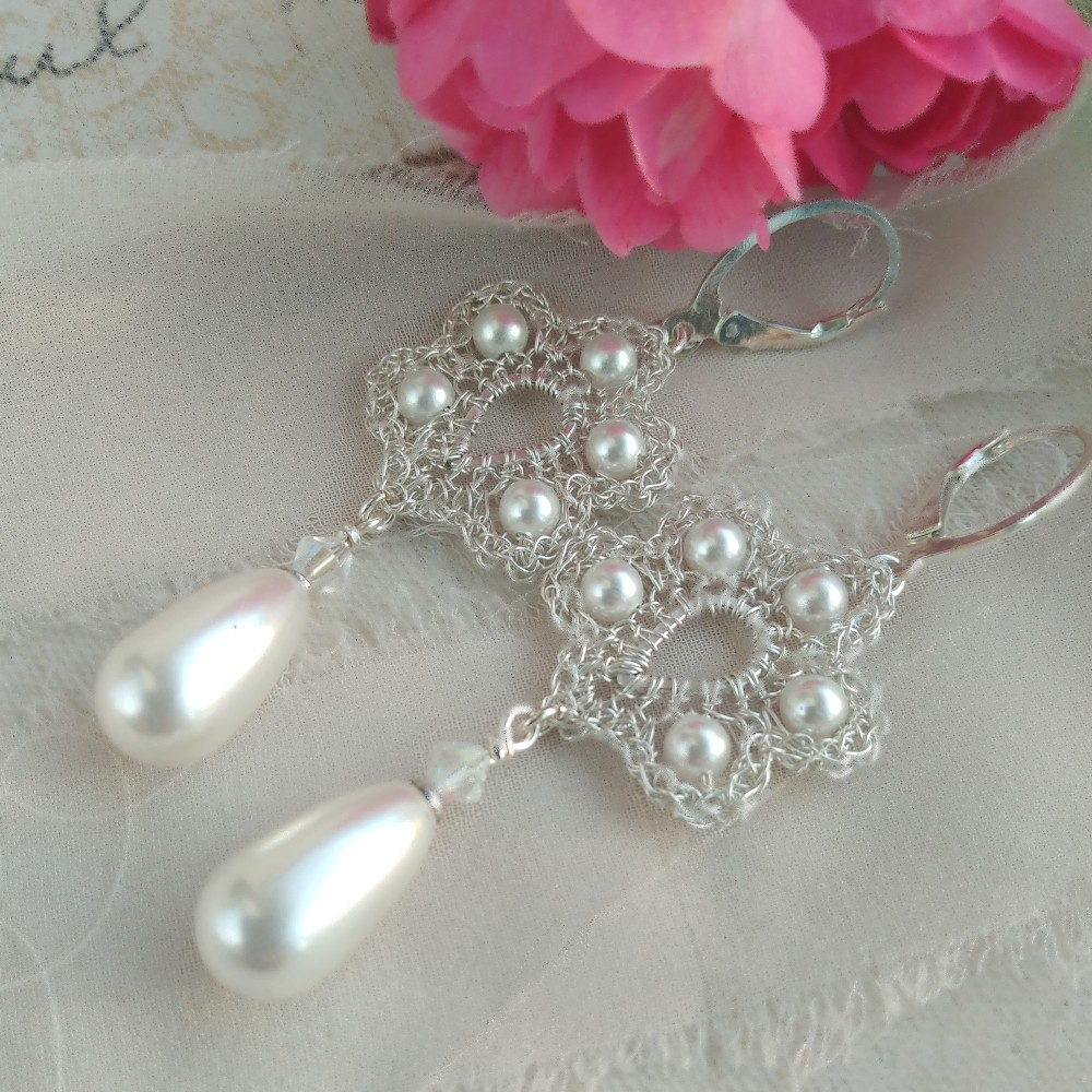 Perollia kolczyki ślubne widać napierwszym planie. Perełki otoczone srebrnymi koronkami. Wgórnej części różowy kwiat.